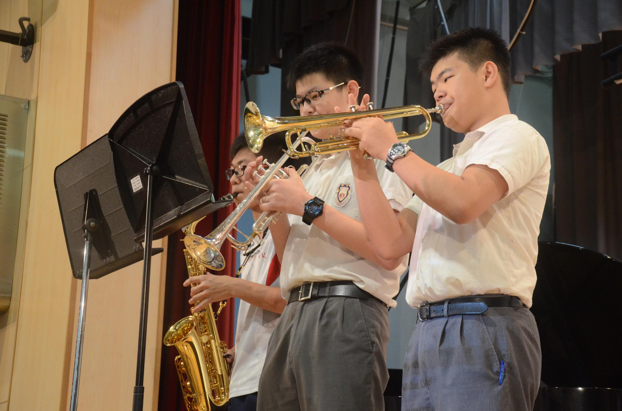 3D Wong Chun Lok is playing the saxophone. 3D Yung Mo Kin and 3F Yau You Wah are playing the trumpets.