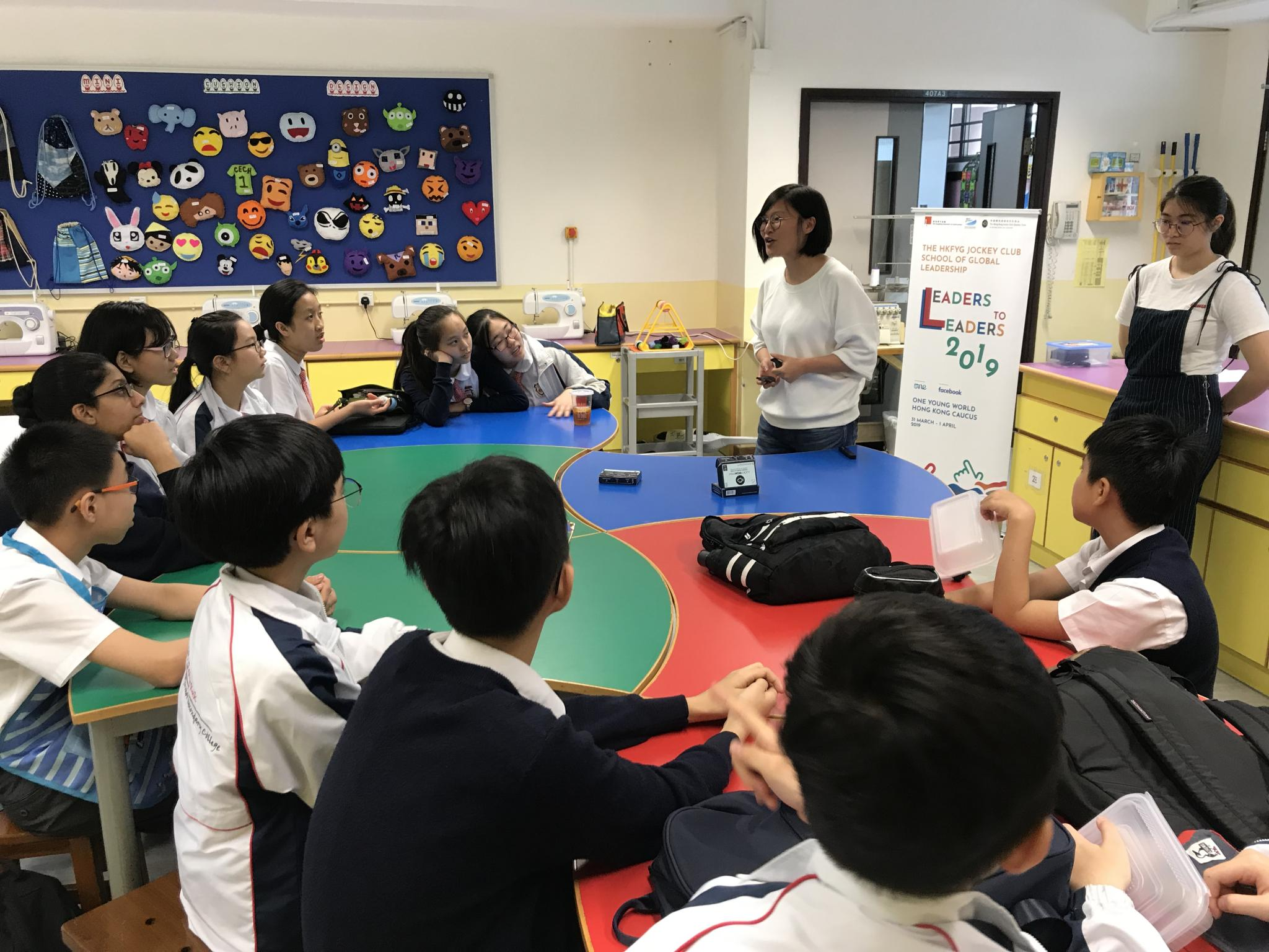 A staff from HKFYG is explaining what a Lucky Iron Fish is to the students.