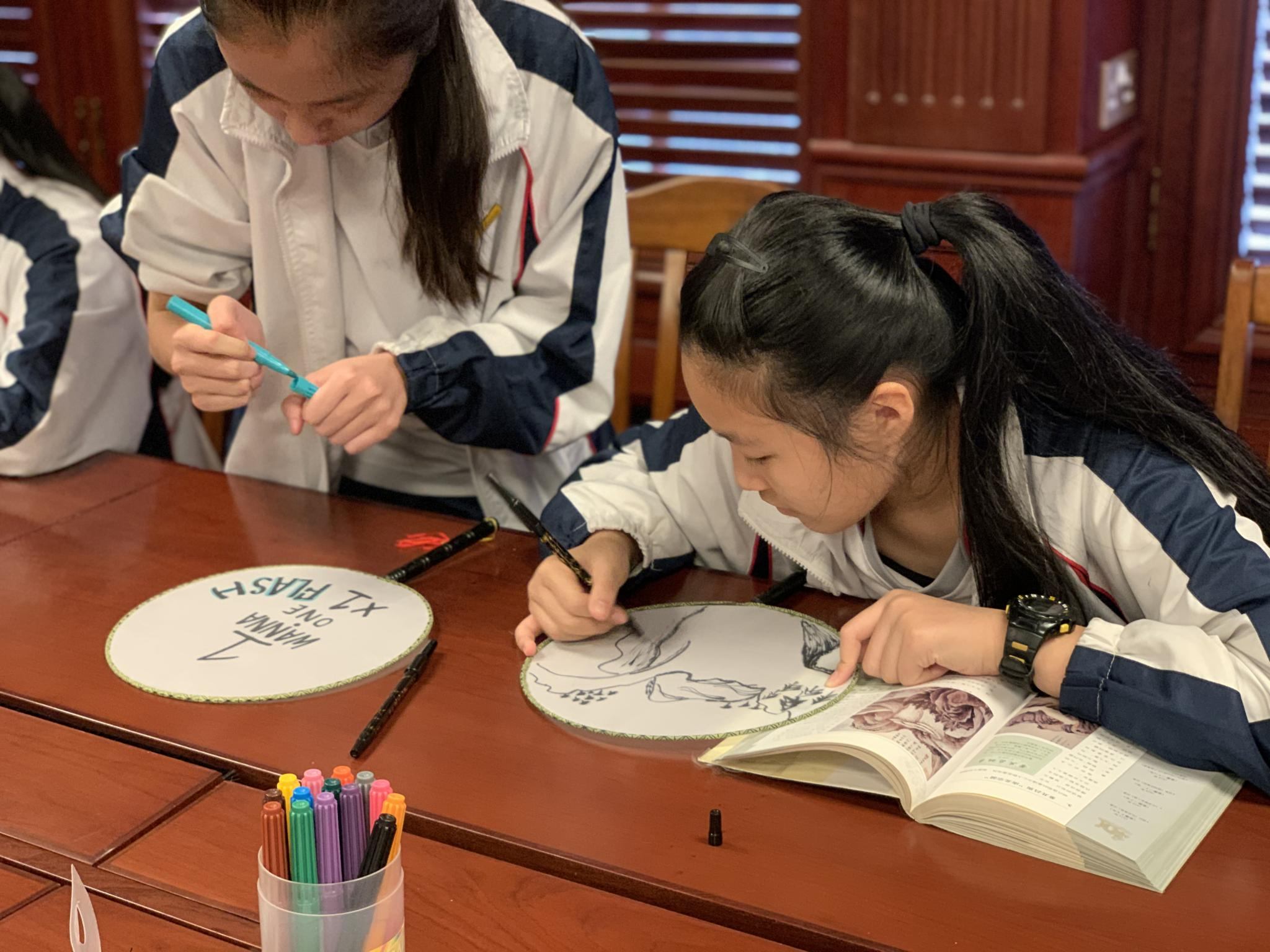 The girl is getting inspiration from the books about Chinese painting.