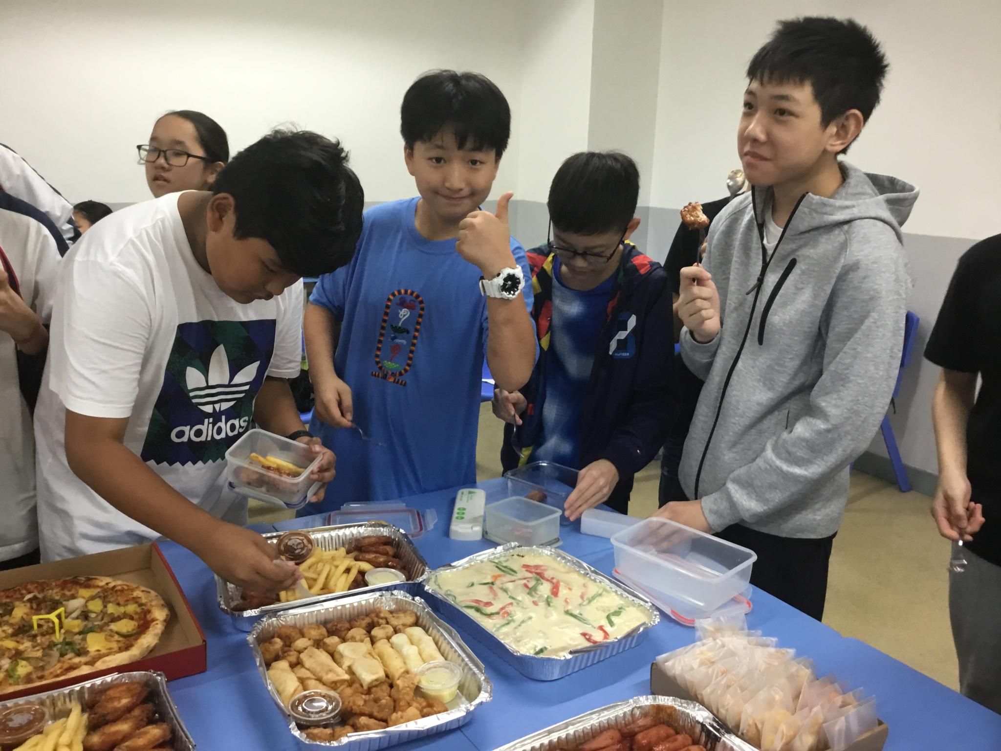 Students are sharing their food happily during the Christmas party. They all bring their own reusable utensils.